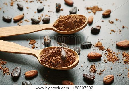 Spoons with aromatic cocoa powder and beans, closeup
