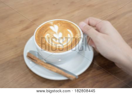 Hand On Hot Cup Of Coffee Latte stock photo