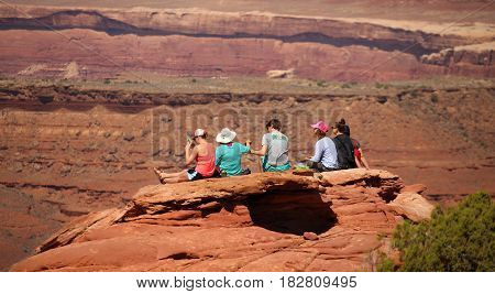 MOAB, UTAH, APRIL 15, 2017 - Young tourists sit on a rock ledge, enjoying the outdoors in Utah.