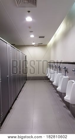 line of white automatic porcelain urinals in public toilets