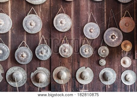 Old Gongs and Chipped Cymbal on Wood Wall