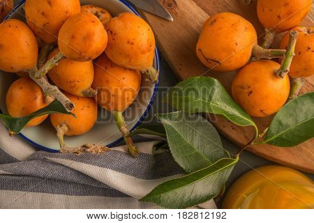 Ripe loquats fruits on kitchen counter background.