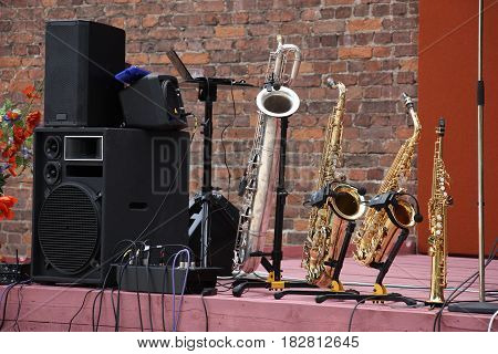 On a street wooden platform there is a sound equipment and four different saxophones. A background a brick wall.