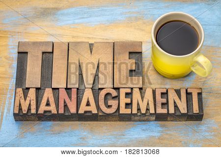 time management word abstract in letterpress wood type printing blocks with a cup of coffee