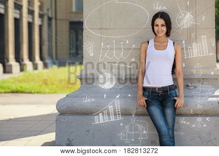 Young confident, beautiful, brunette girl stands near wall, pending infographic