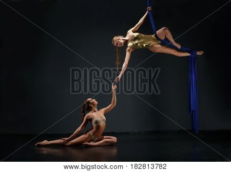Young pretty female gymnasts exercising on blue aerial silks studio shot