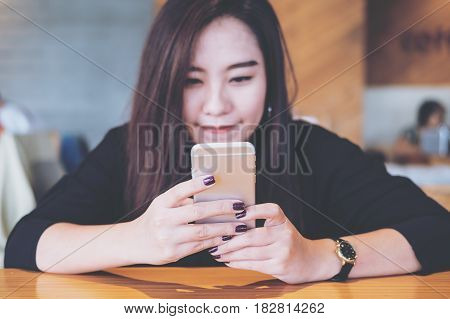 A beautiful Asian girl with smiley face holding and using smart phone in modern cafe