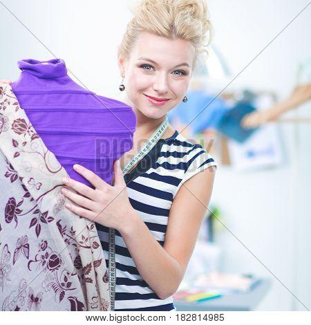 fashion designer standing near mannequin in office