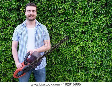 Hobbyist  Gardner  Using An Hedge Clipper In The Home Garden