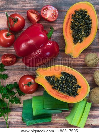 Assortment of fresh fruits and vegetables on wooden  background