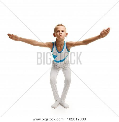 Portrait of little male gymnast doing exercises on white background