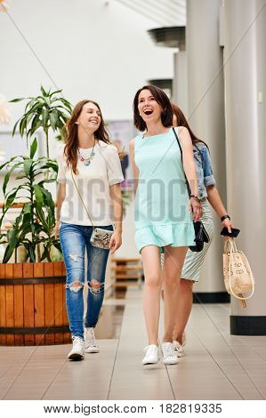 Three happy smiling friends walking in shopping center and choosing clothes