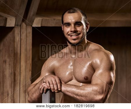 Portrait of happy smiling young muscular bodybuilder in gym