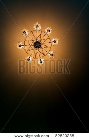 Bottom view electric ceiling lamp shines with yellow light