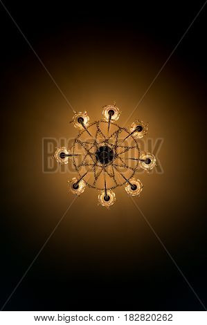 View from below electric ceiling lamp shines with yellow light