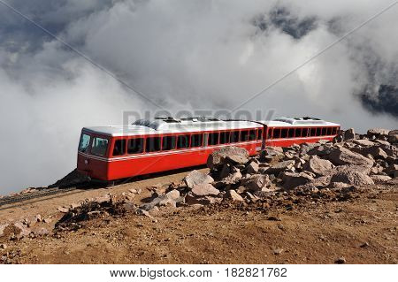 Tram carries tourists up the steep incline of Pikes Peak through the clouds
