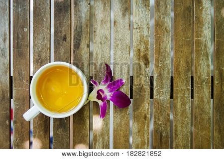 Violet dendrobium orchid flower beside a jasmine ceramic tea cup on wooden table.Top view vertical texture.