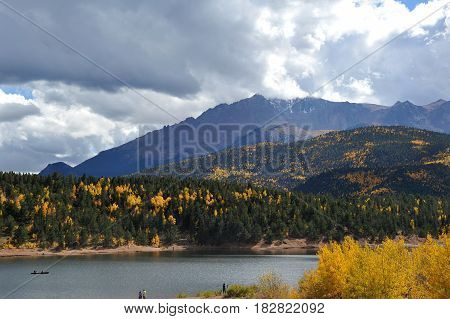 A view of Pikes Peak crested with snow and surrounded by storm clouds as seen from below behind Cyrstal Resevoir.