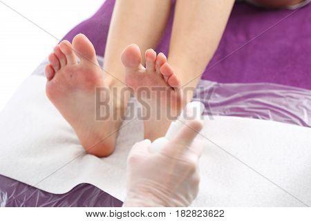 Foot hygiene Podology, preparation of feet for surgery Skin disinfection, beautician disinfects the feet of women with the preparation