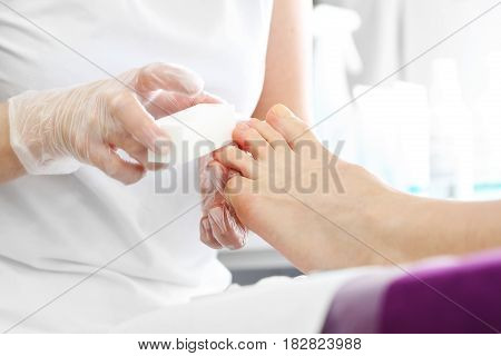 Nail care, Foot care. Pedicure, beautiful healthy nails. Sawing nails, woman with a beautician. Woman in a beautician at a pedicure