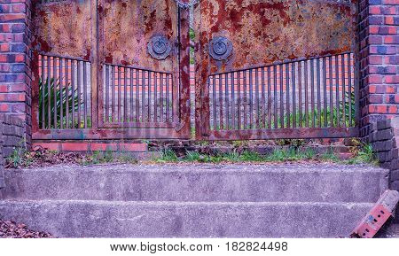 View of stairs leading to a chained rusted gate with red brick columns on each side located at old abandoned picnic pavilion in woodland area in South Korea.