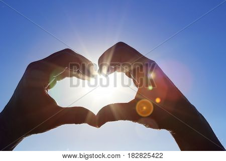 Silhouette of wet hands in heart shape with sunning sun