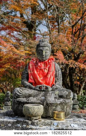 Stone statue of Buddha with autumn colored leaves in Adashino Nenbutsuji Temple Kyoto, Japan