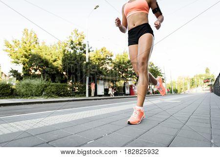 Athletic woman running on sidewalk, cropped image.