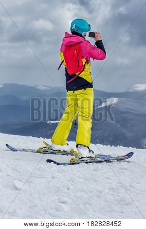 Rear view of sportsman with snowboard watching the nature. Skier on top of a mountain