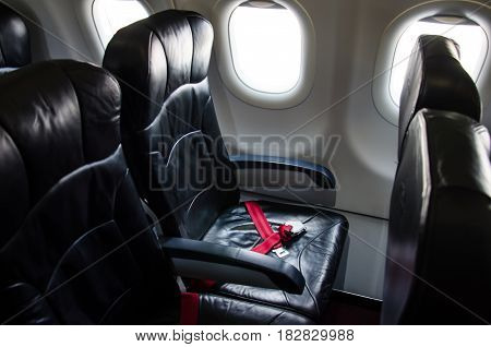 Seat belt on seat shot in airplane with Black seat.