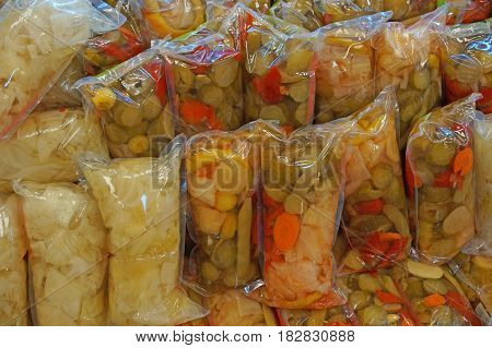 Canned vegetables in polyethylene packages are sold on the counter of a vegetable store.