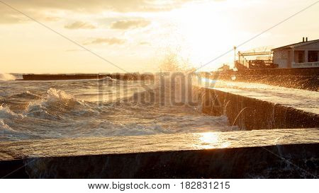 Picturesque seascape. The raging sea the waves break against the breakwater. The sun shines through the waves. On the shore are buildings. Sunset.
