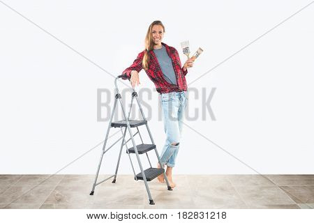 Beautiful young woman in working clothes holding paintbrushes, standing near step ladder, smiling happily, ready for home renovation.