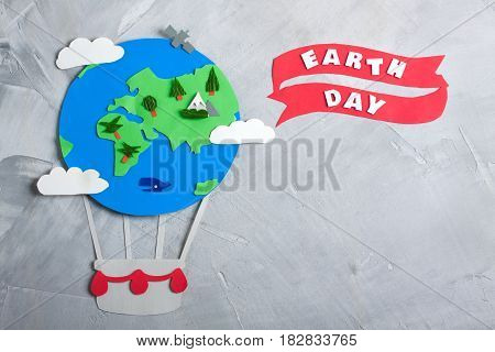 Paper craft earth globe handmade on gray concrete background. Earth day concept lettering. Horizontal orientation top view.