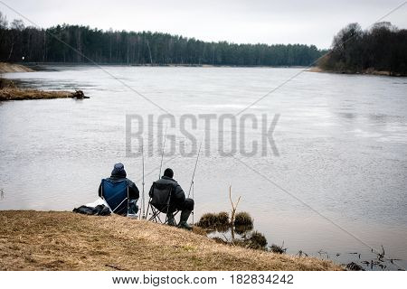CARNIKAVA LATVIA - APRIL 1 2017: Two unknown men with a pole catch fish from the river shore.