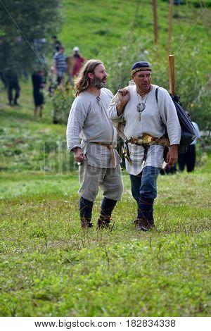TERVETE LATVIA - AUGUST 13 2011: Historical Zemgalu days. Unknown men in historical dress standing in the meadow and talking.