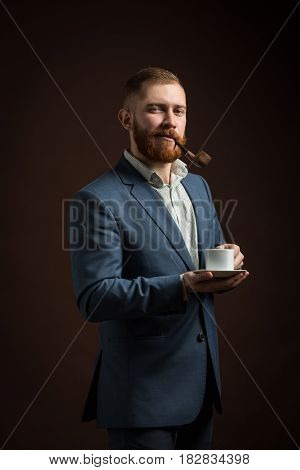 Portrait of handsome man with ginger beard holding cup of coffee while smoking pipe