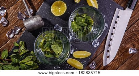 Two glasses, mint, lime, knife and ice on black stone board