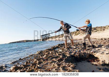 Senior man fishing with his grandson
