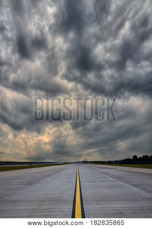 Empty airport runway with stormy clouds on the background
