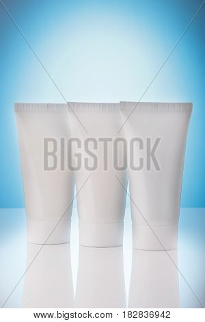 Three tubes with skin care at light blue background