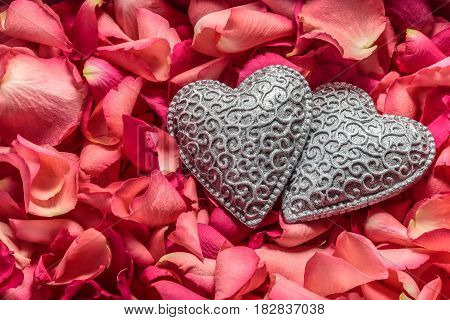 Two decorative carved hearts at red rose petals background