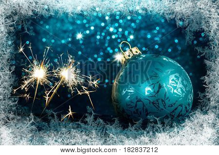 Decorative Christmas tree ball in front of sparkling background with ice crystals frame