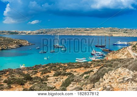 Comino Malta - Panoramic skyline view of the famous and beautiful Blue Lagoon on the island of Comino with sailboats traditional Luzzu boats and tourists enjoying the azure mediterranean sea water and sunshine
