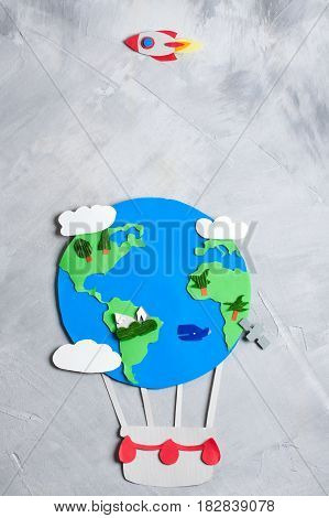 Paper craft earth globe rocket handmade on gray concrete background. Earth day concept. Vertical orientation top view.