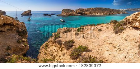 Comino Malta - The beautiful Blue Lagoon with turquoise clear sea water yachts and snorkeling tourists on a sunny summer day with the island of Gozo at background