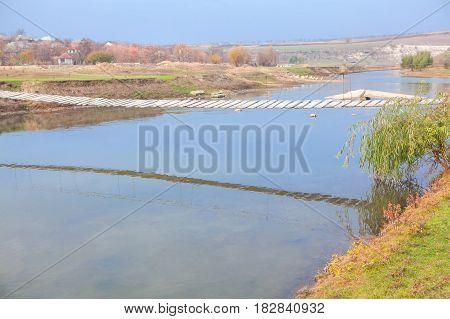 rustic scene with wooden pedestrian bridge over river