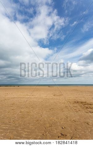 Sandy beach with blue sky at low tide at Benllech in Anglesey North Wales