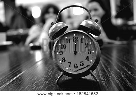 Vintage clock on wooden background. Black and white