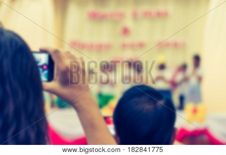 blur image of parent take photo of kid 's show on stage with smartphone at school for background usage .